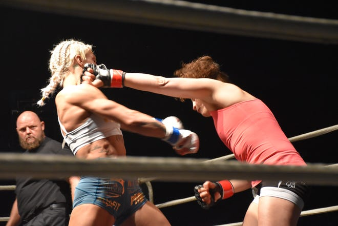 Hannah Goldy, left, avoids the brunt of left hook from Shannan Goughary in the main event, MMA bout Saturday at Island 50 at the Pensacola Bay Center. It was the first women's main event in Island Fights history.