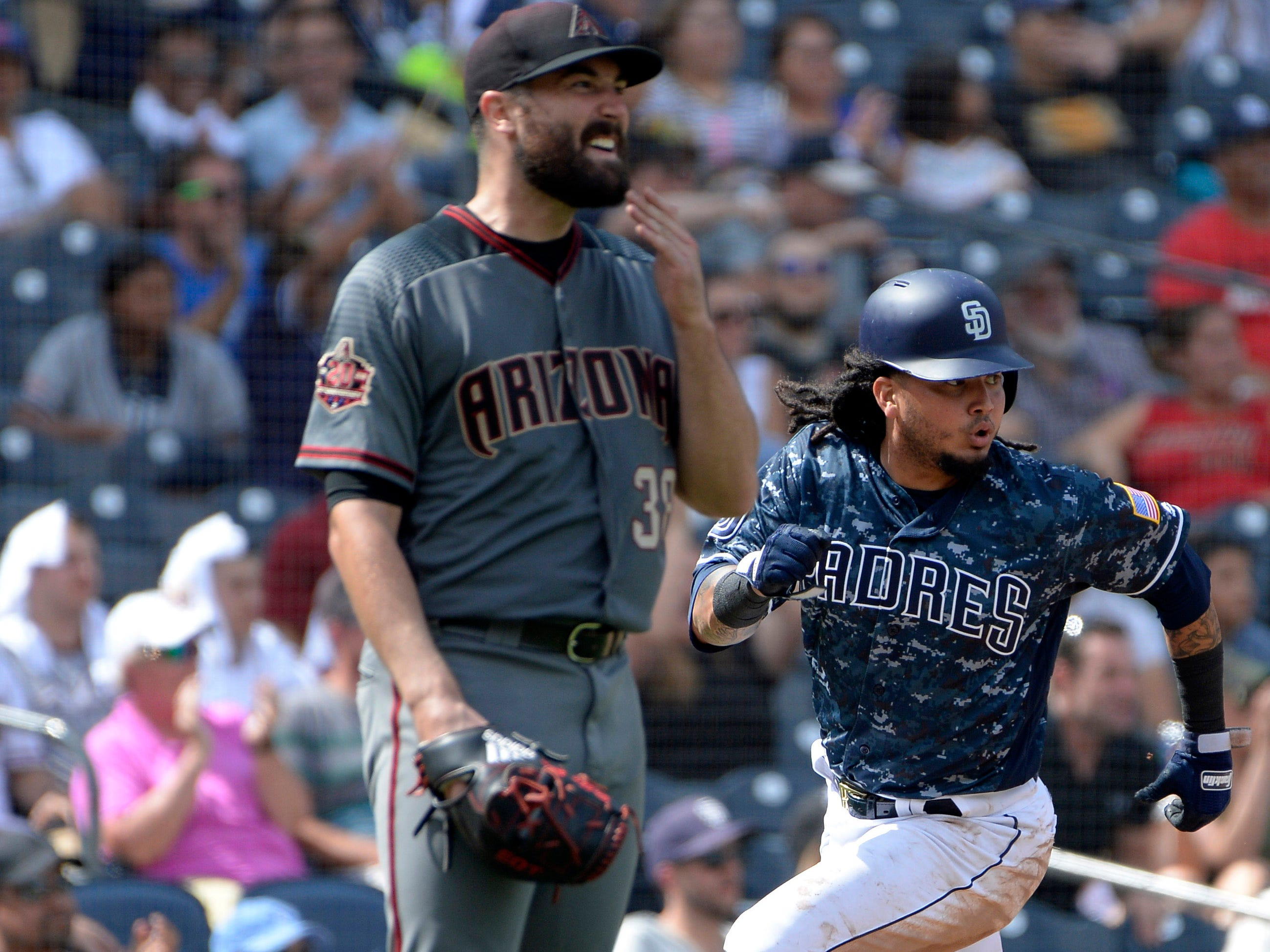 Sep 30, 2018; San Diego, CA, USA; San Diego Padres shortstop Freddy Galvis (right) runs to score as Arizona Diamondbacks starting pitcher Robbie Ray (left) reacts in the fifth inning at Petco Park. Mandatory Credit: Jake Roth-USA TODAY Sports