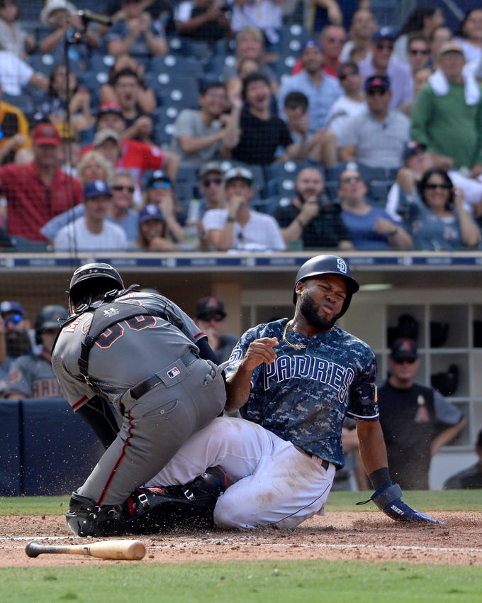 Sep 30, 2018; San Diego, CA, USA; San Diego Padres center fielder Manuel Margot (right) is tagged out by Arizona Diamondbacks catcher John Ryan Murphy (left) in the eighth inning at Petco Park. Mandatory Credit: Jake Roth-USA TODAY Sports