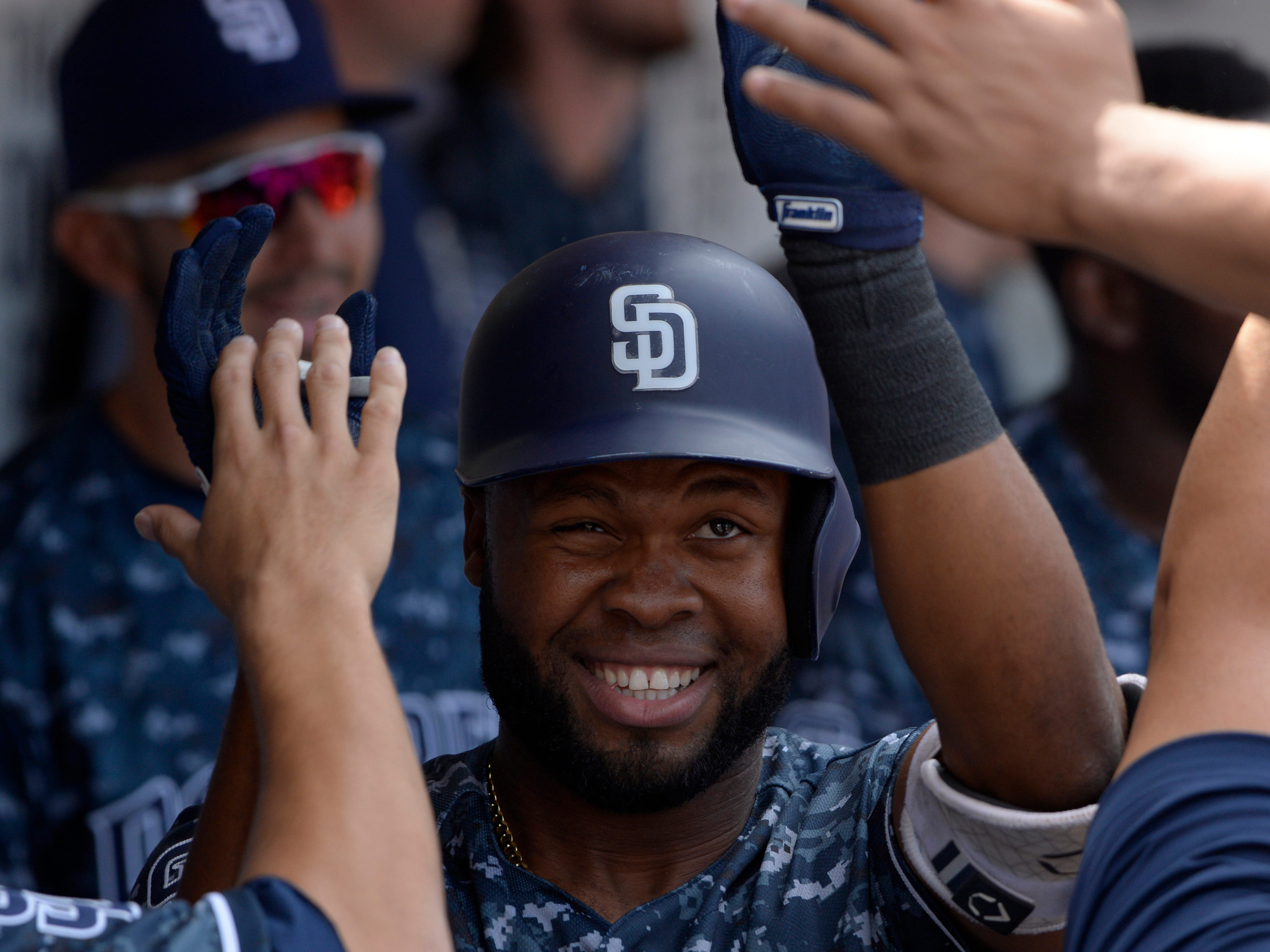 Sep 30, 2018; San Diego, CA, USA; San Diego Padres center fielder Manuel Margot (center) is congratulated after hitting a solo home run during the second inning against the Arizona Diamondbacks at Petco Park. Mandatory Credit: Jake Roth-USA TODAY Sports