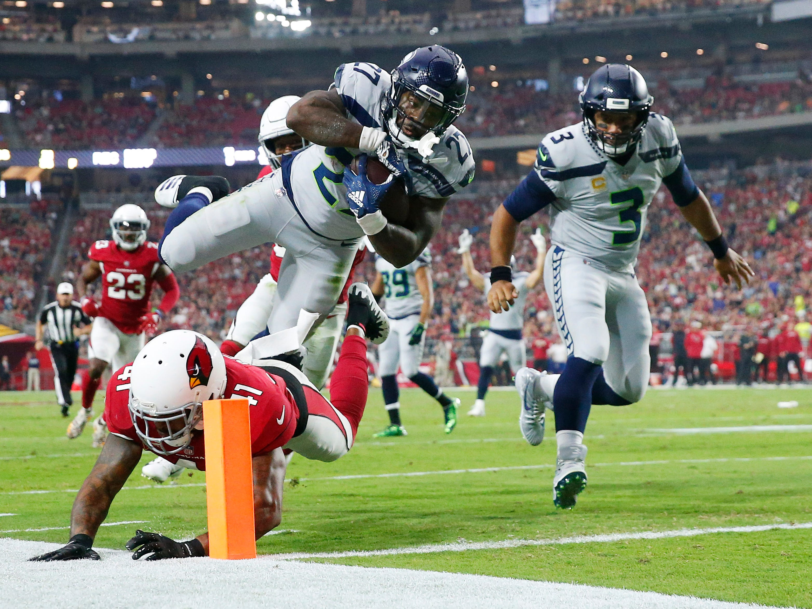 Seattle Seahawks running back Mike Davis (27) scores over Arizona Cardinals defensive back Antoine Bethea (41) during the first quarter at State Farm Stadium in Glendale, Ariz. September 30, 2018.