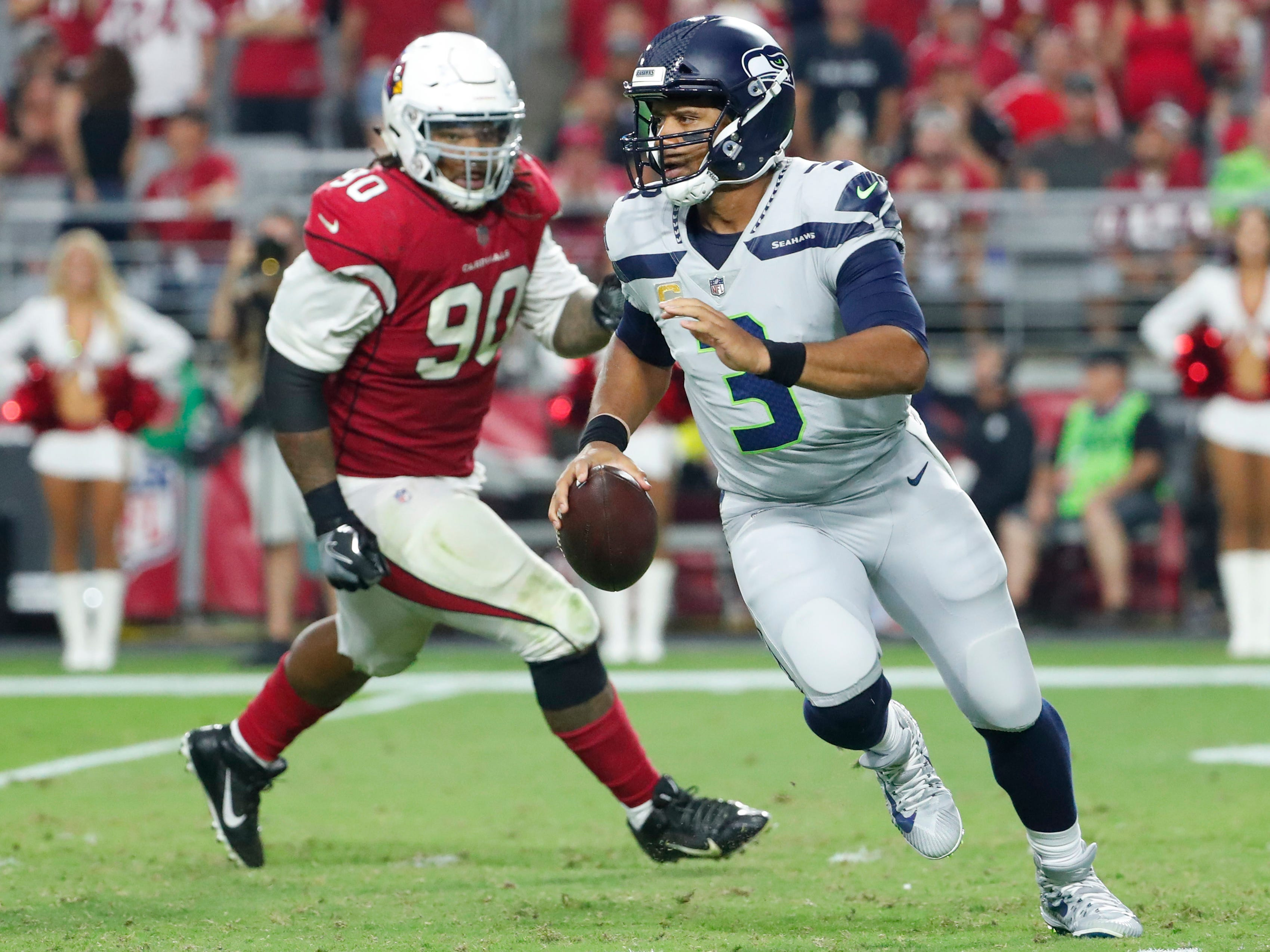 Seattle Seahawks quarterback Russell Wilson (3) scrambles away from Arizona Cardinals defensive tackle Robert Nkemdiche (90) during the second quarter at State Farm Stadium in Glendale, Ariz. September 30, 2018.