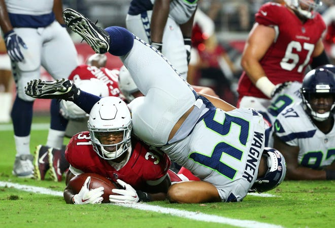 Arizona Cardinals running back David Johnson dives and scores a touchdown against the Seattle Seahawks in the first half at State Farm Stadium in Glendale, Ariz.