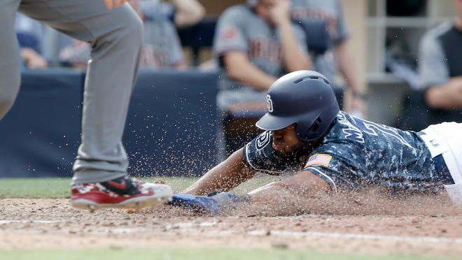 San Diego Padres' Manuel Margot, right, slides into home safely after Arizona Diamondbacks catcher John Ryan Murphy threw to first to get Francisco Mejia after striking out swinging during the 10th inning of a baseball game in San Diego, Sunday, Sept. 30, 2018. The Padres won 4-3 in 10 innings.