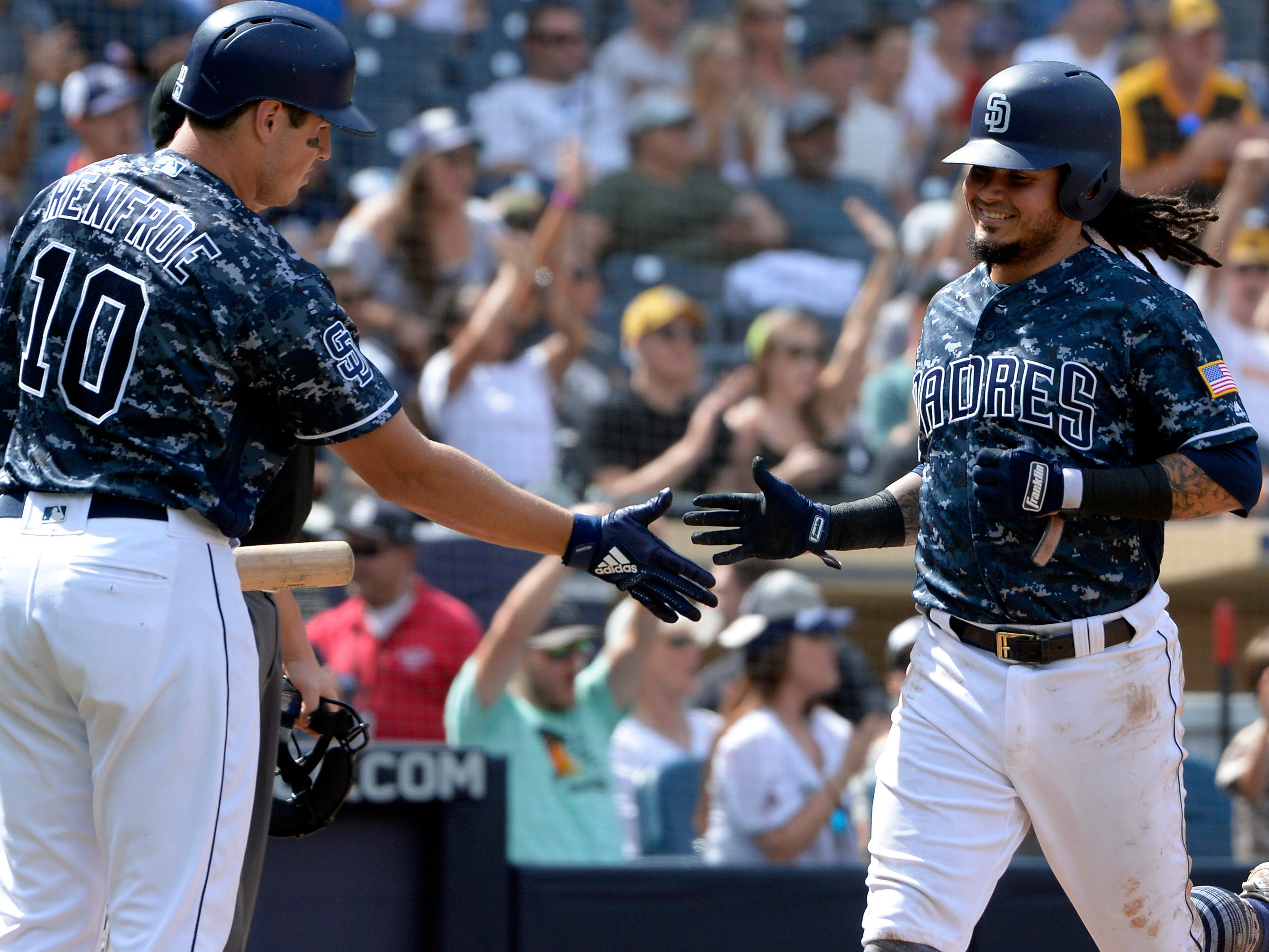 Sep 30, 2018; San Diego, CA, USA; San Diego Padres shortstop Freddy Galvis (right) is congratulated by left fielder Hunter Renfroe (10) after scoring on a double by right fielder Franmil Reyes (not pictured) during the fifth inning against the Arizona Diamondbacks at Petco Park. Mandatory Credit: Jake Roth-USA TODAY Sports