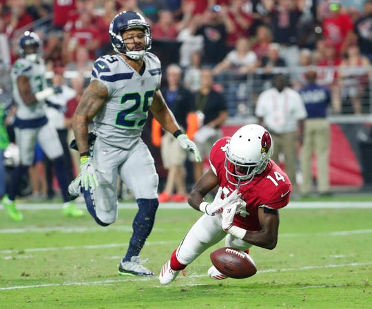 Arizona Cardinals wide receiver J.J. Nelson (14) drops a pass while defended by Seattle Seahawks defensive back Earl Thomas (29) during the second quarter at State Farm Stadium in Glendale, Ariz. September 30, 2018.