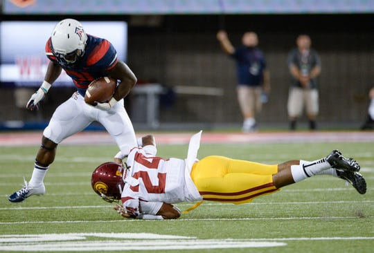 Sep 29, 2018; Tucson, AZ, USA; Arizona Wildcats running back J.J. Taylor (21) is brought down by Southern California Trojans cornerback Isaiah Langley (24) at Arizona Stadium. Mandatory Credit: Casey Sapio-USA TODAY Sports