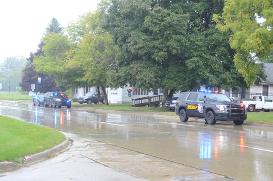 Law enforcement waits outside a home on the 2600 block of Oak Street as authorities search for a suspect in a domestic shooting Sunday morning in Port Huron Township.