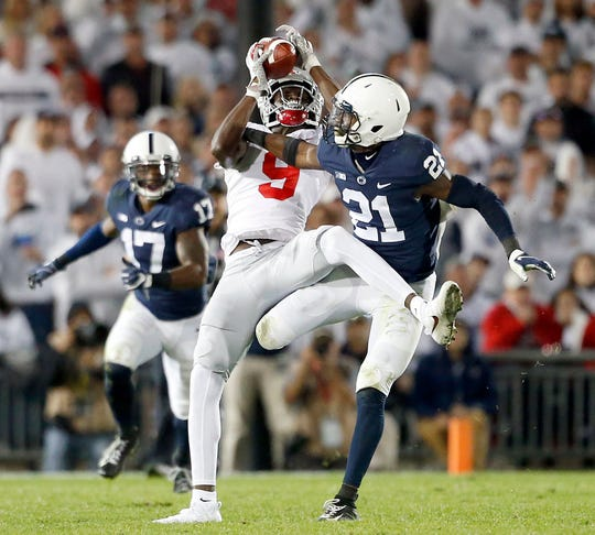 Ohio State's Binjimen Victor (9) catches a pass in front of Penn State's Amani Oruwariye (21) and runs in for a touchdown during the second half of an NCAA college football game in State College, Pa., Saturday, Sept. 29, 2018. Ohio State won 27-26.