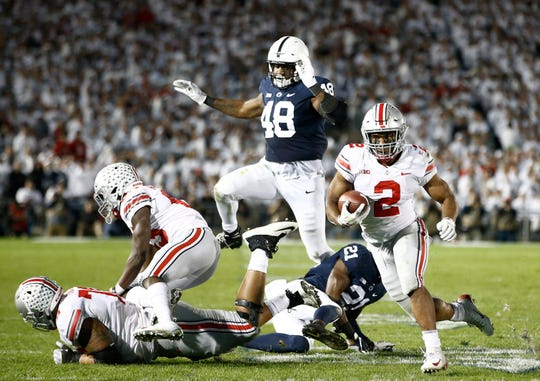 Ohio State's J.K. Dobbins (2) runs the ball as Penn State's Shareef Miller (48) gives chase during the first half of an NCAA college football game in State College, Pa., Saturday, Sept. 29, 2018.
