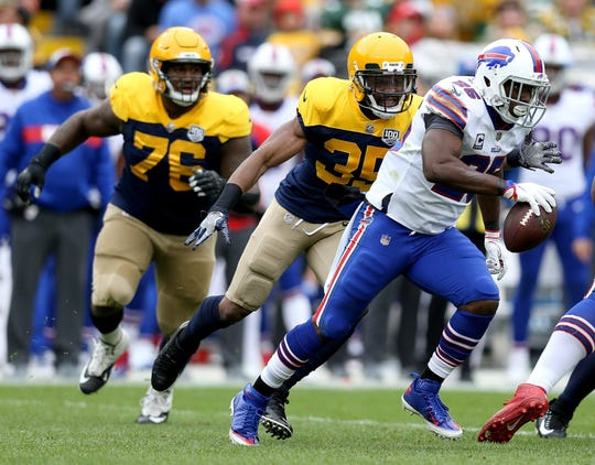 LeSean McCoy of the Buffalo Bills runs away from Jermaine Whitehead of the Green Bay Packers and Mike Daniels during the first quarter.