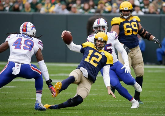 Green Bay Packers' Aaron Rodgers runs for a first down during the first half.