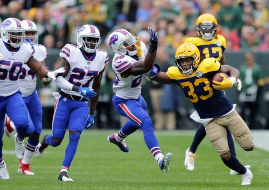 Green Bay Packers running back Aaron Jones stiff arms Buffalo Bills defensive back Rafael Bush during the first quarter.