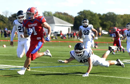 Fairport's Dante Coccia, left, outruns Webster Thomas' Noah Benedict for the Red Raiders' first touchdown during a regular season game played at Fairport High School, Saturday, Sept. 29, 2018.