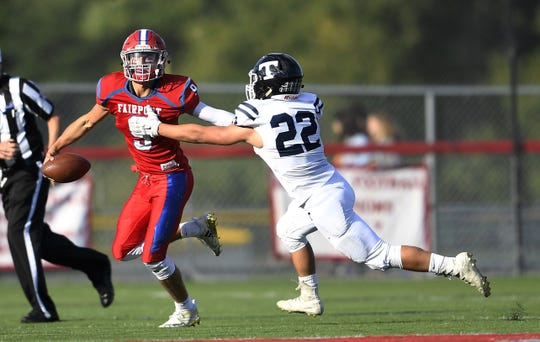 Fairport's Mike Pellittiere, left, stiff arms Webster Thomas' Ethan Harold during a regular season game played at Fairport High School, Saturday, Sept. 29, 2018.