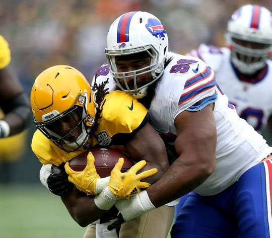 Aaron Jones of the Green Bay Packers is tackled by Star Lotulelei of the Buffalo Bills during the second quarter.