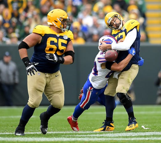 Aaron Rodgers of the Green Bay Packers fumble as he is sacked by Taron Johnson  of the Buffalo Bills during the fourth quarter of Sunday's game at Lambeau Field.