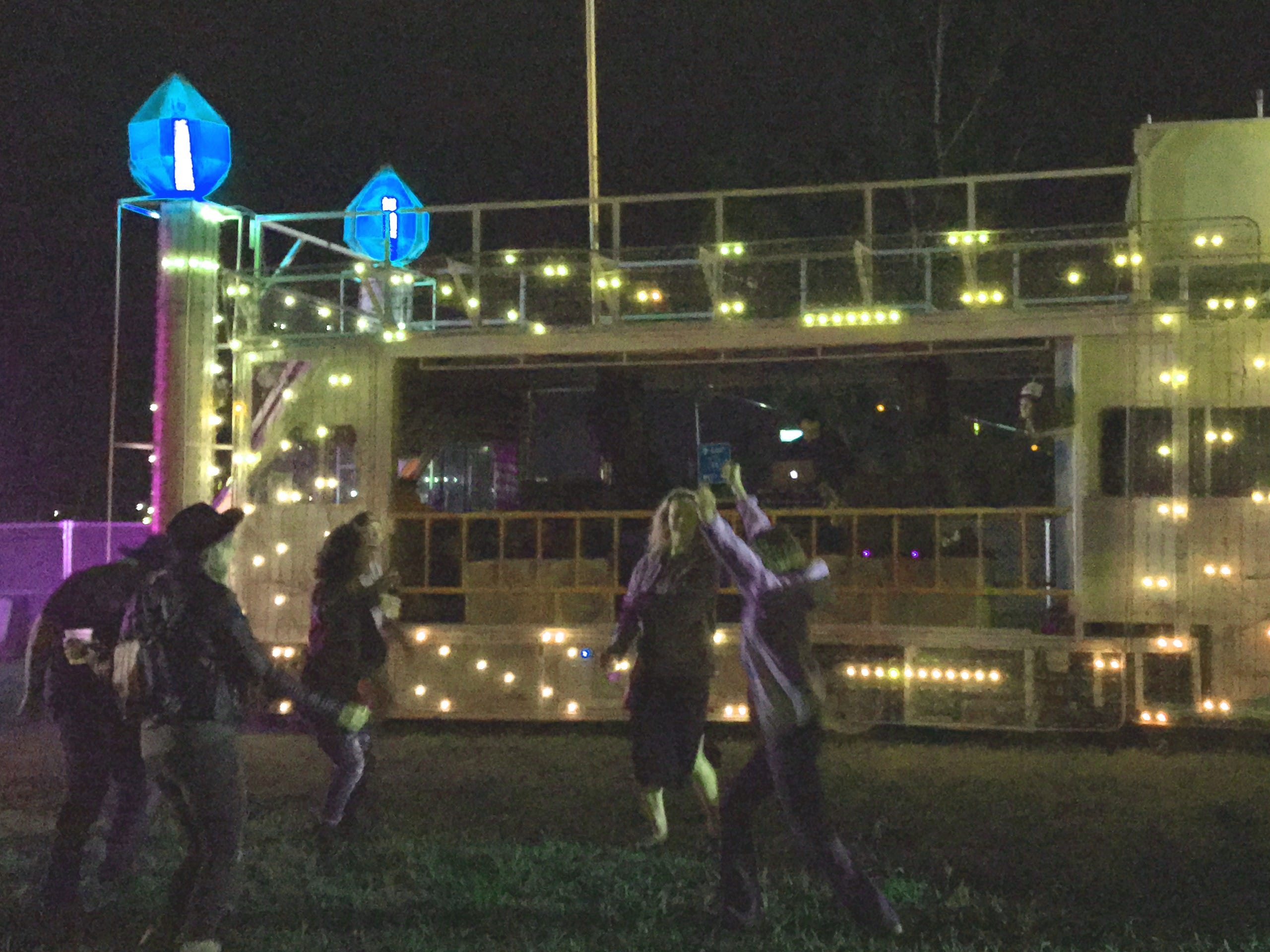 Festival-goers dance in front of an art car Saturday night.