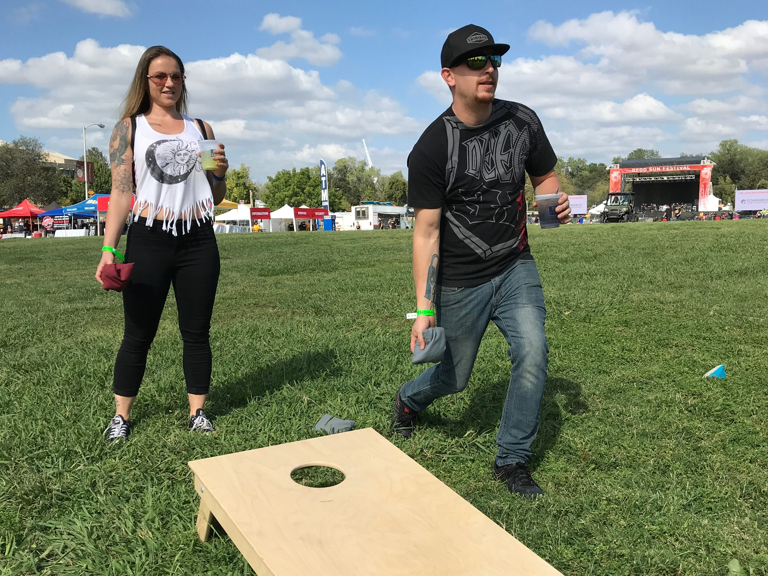 Rhiyah Rogers, left, watches Stephen Bull toss a bean bag in cornhole competition Saturday before the music started at the Redd Sun Festival at the Redding Civic Auditorium.