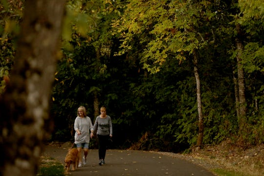 Friends Jeanne Williams, left, and Kim Clark, both of Salem, walk Williams' golden retriever Zoe as the tree leaves change color at Minto-Brown Island Park in Salem on Sunday, Sept. 30, 2018.