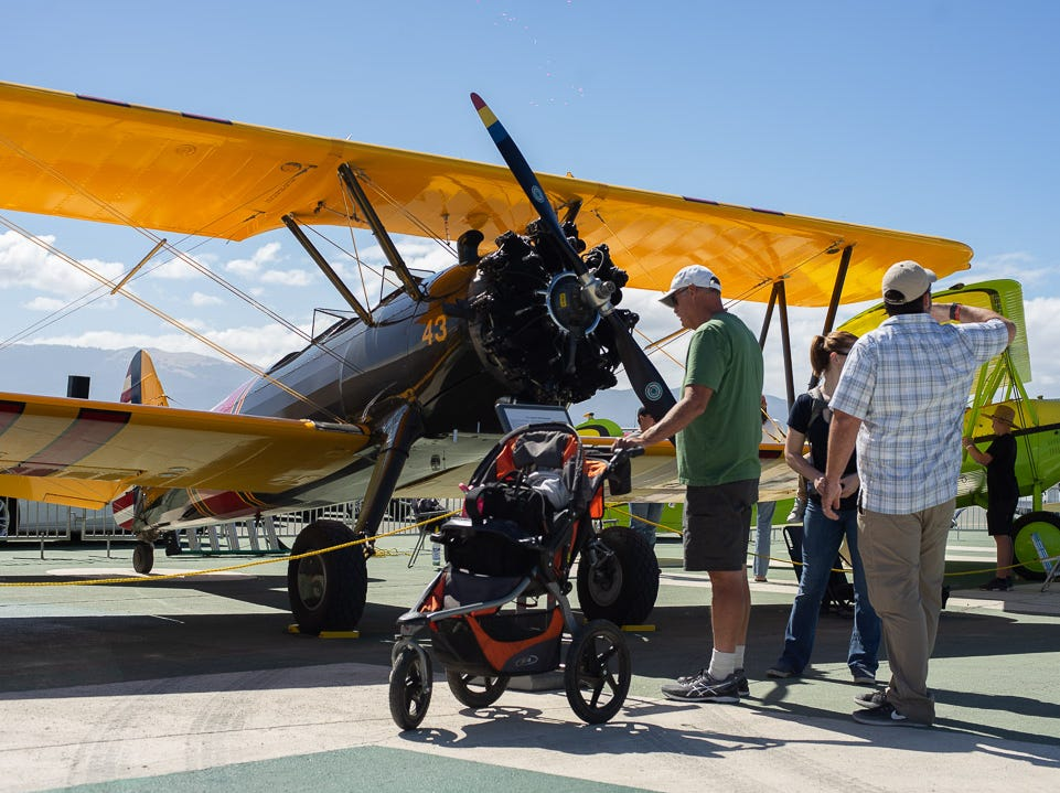 """Spectator reading about the U.S Army PT-13D """"Stearman"""" during the California International Airshow Salinas at the Salinas Municipal Airport on Saturday, September 29, 2018."""