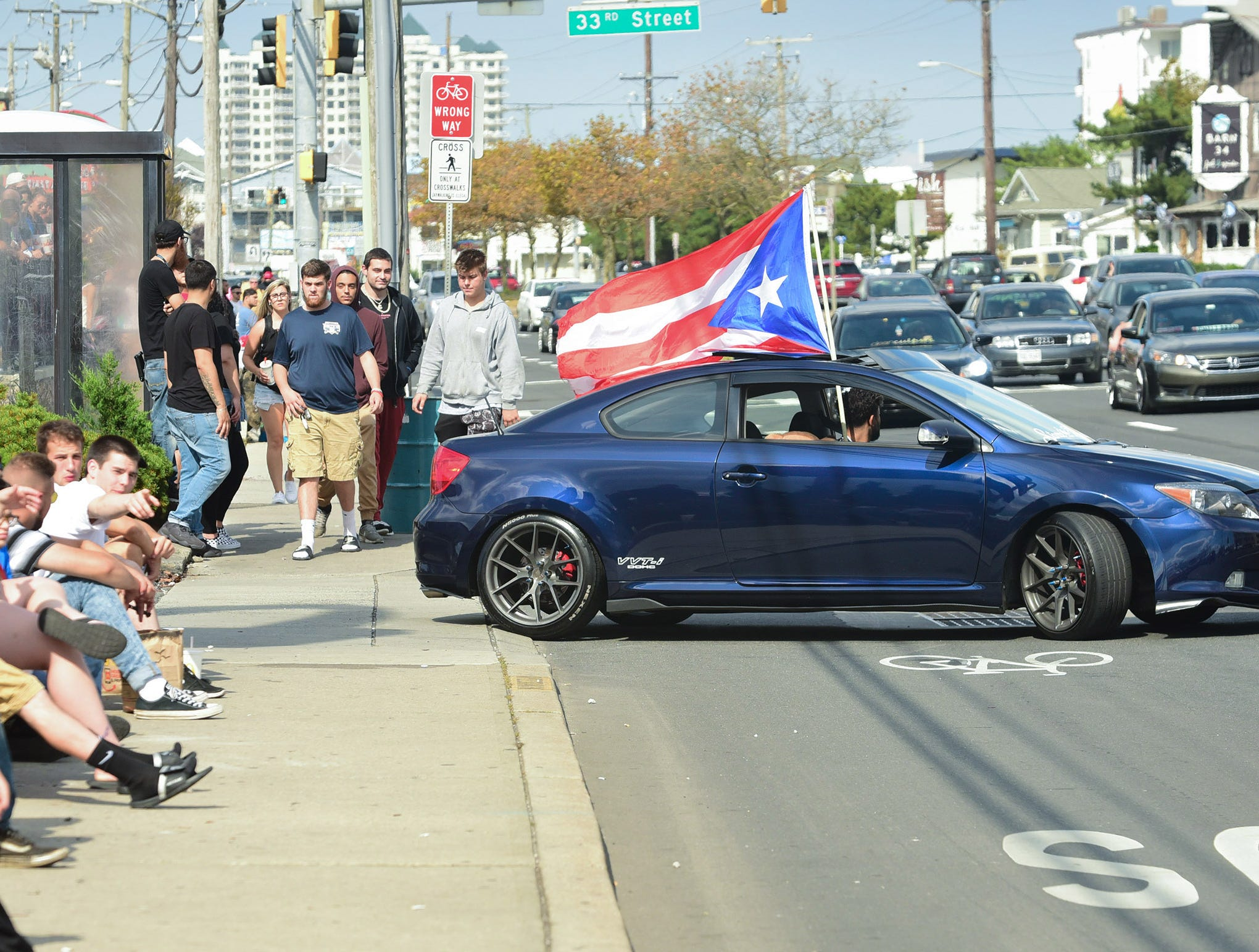 Spectators watch participants of the unofficial H2Oi event cruise down Coastal Highway in Ocean City on Saturday, Sept. 29, 2018.