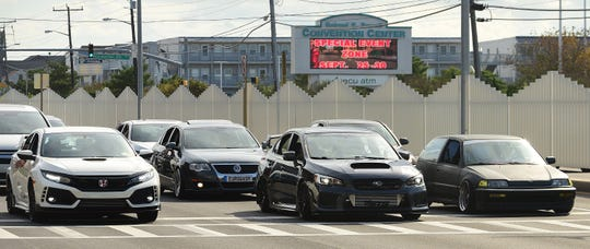 With the Special Event Zone sign flashing in the background, participants of the unofficial H2Oi event cruise down Coastal Highway in Ocean City on Saturday, Sept. 29, 2018.