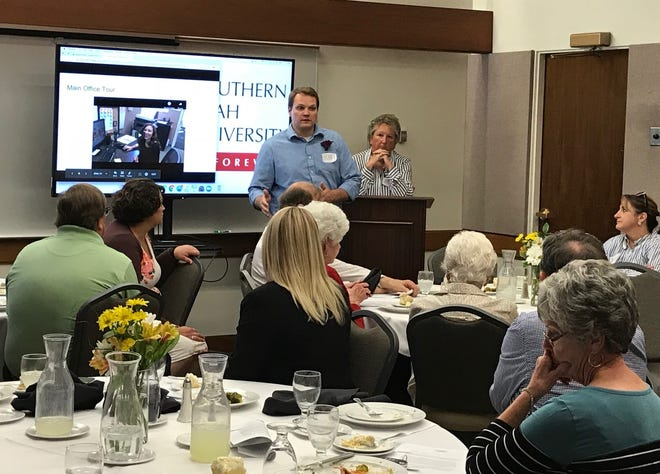 Dr. Brant Wadsworth, executive director of Canyon Creek Services, shares a video tour of the center at the annual board luncheon. Board President Bev Emery looks on.