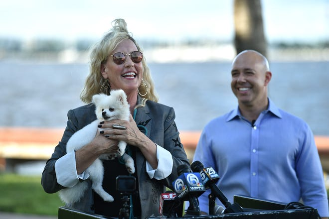 Environmental activist Erin Brockovich and U.S. Rep. Brian Mast, R-Palm City, speak to a crowd at Flagler Park in Stuart advocating for clean water on Sunday, September 30, 2018. Brockovich is holding Pandora, a dog that got sick after eating a dead fish next to the St. Lucie River in Stuart.