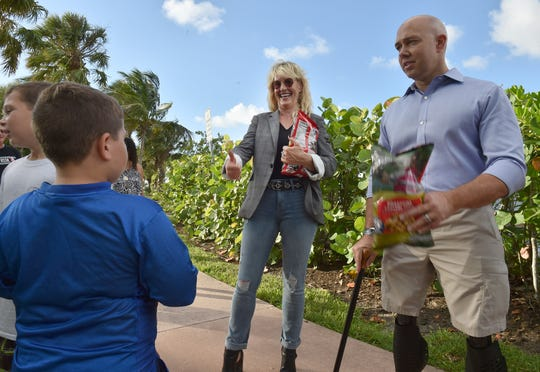Environmental activist Erin Brockovich gestures to Zacharyah Buys, 8, of  Jensen Beach, after he and his brother Zasha, 10, spoke with Brockovich and U.S. Rep. Brian Mast, R-Palm City, on Sunday, September 30, 2018 at Flagler Park in Stuart. Brockovich and Mast spoke to a crowd at the park, advocating for clean water in Stuart.