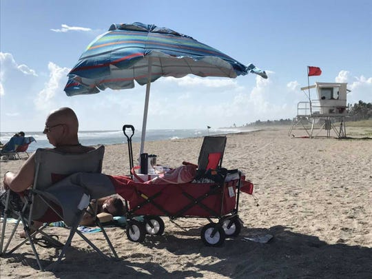 Dan Nickols of Port St. Lucie relaxes Sunday, Sept. 30, 2018, at Bathtub Beach in Martin County as a single red flag on a lifeguard stand warns of high surf. Lifeguards at Bathtub and Hobe Sound Beach also ar on the lookout for a unknown irritant that, like red tide, has caused beachgoers to complain of respiratory problems.