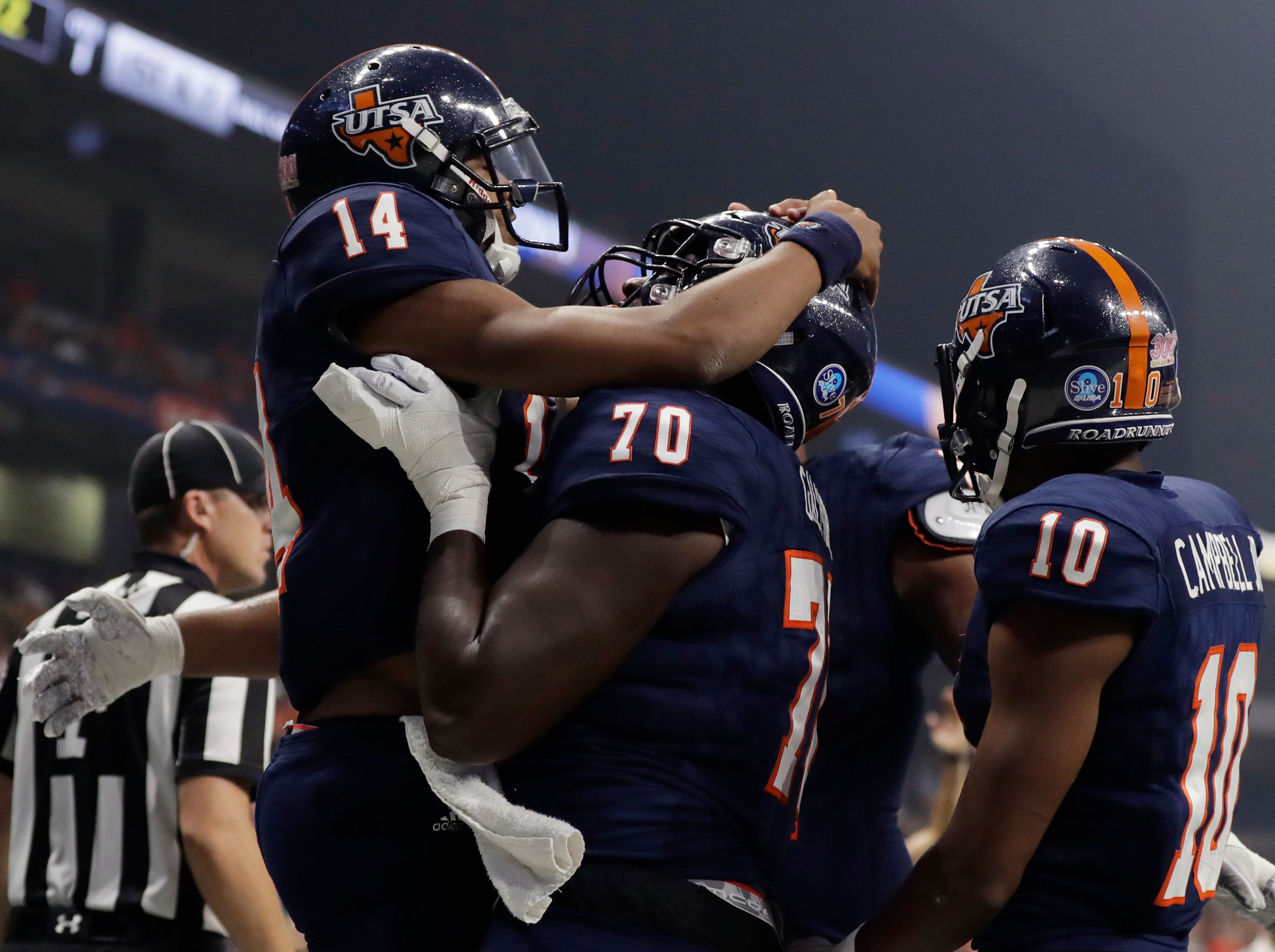 UTSA quarterback Cordale Grundy (14) celebrates his touchdown with teammates Jalyn Galmore (70) and Greg Campbell Jr. (10) during the first half of an NCAA college football game against UTEP, Saturday, Sept. 29, 2018, in San Antonio. (AP Photo/Eric Gay)