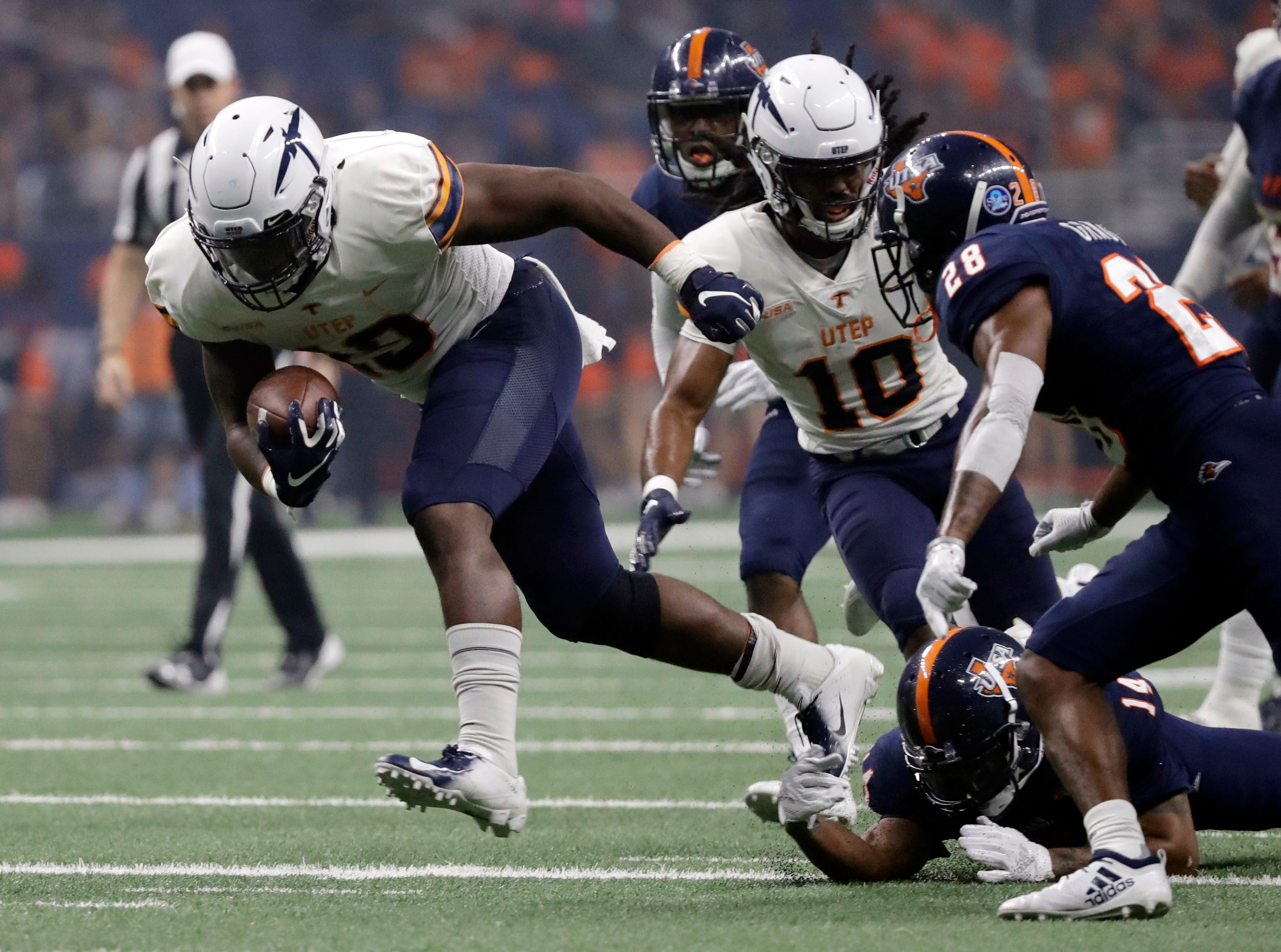 UTEP running back Treyvon Hughes (19) is tripped up by UTSA safety C.J. Levine (14) during the first half of an NCAA college football game Saturday, Sept. 29, 2018, in San Antonio. (AP Photo/Eric Gay)