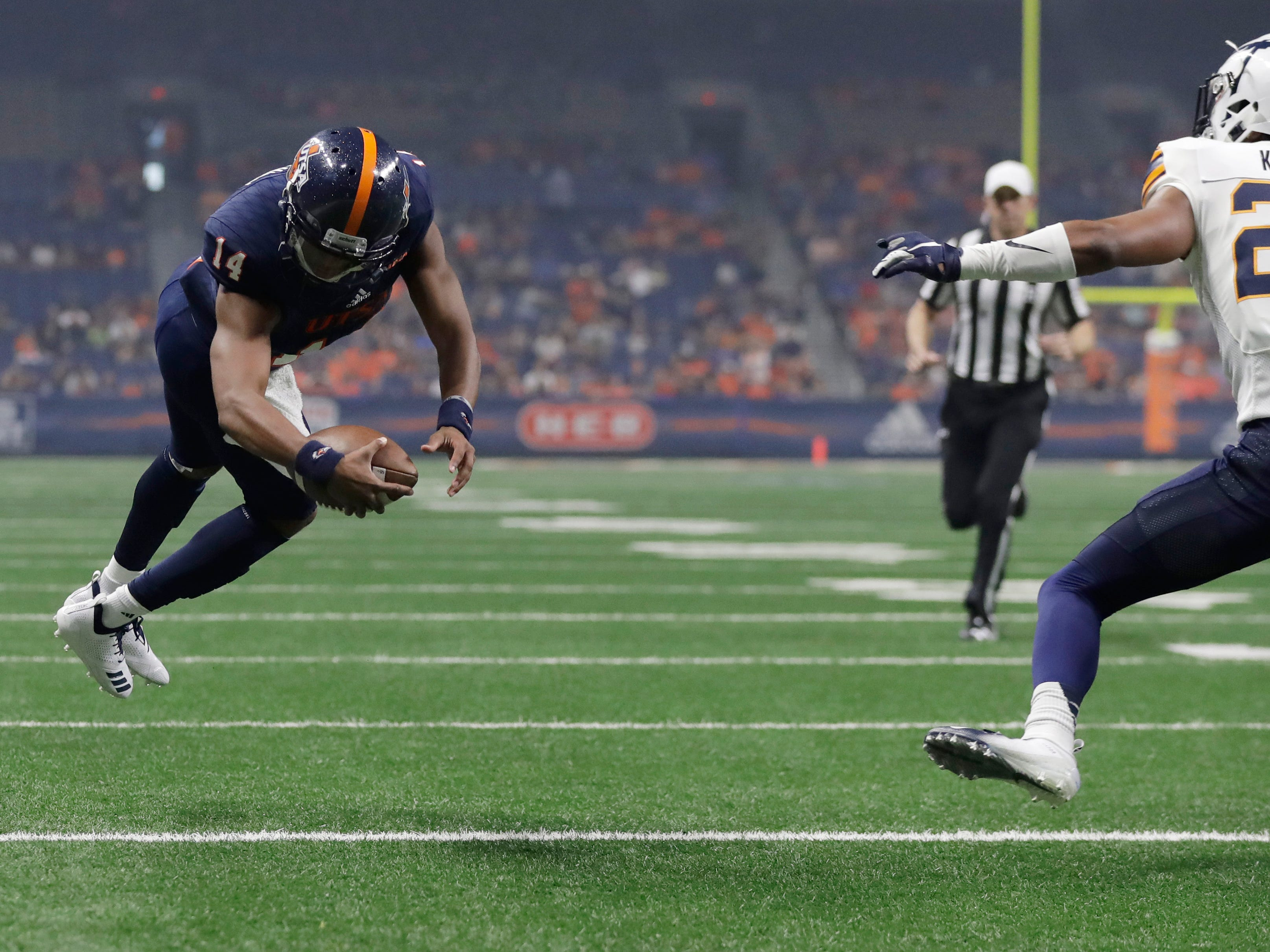 UTSA quarterback Cordale Grundy (14) dives for a touchdown past UTEP defensive back Kahani Smith (24) during the first half of an NCAA college football game Saturday, Sept. 29, 2018, in San Antonio. (AP Photo/Eric Gay)