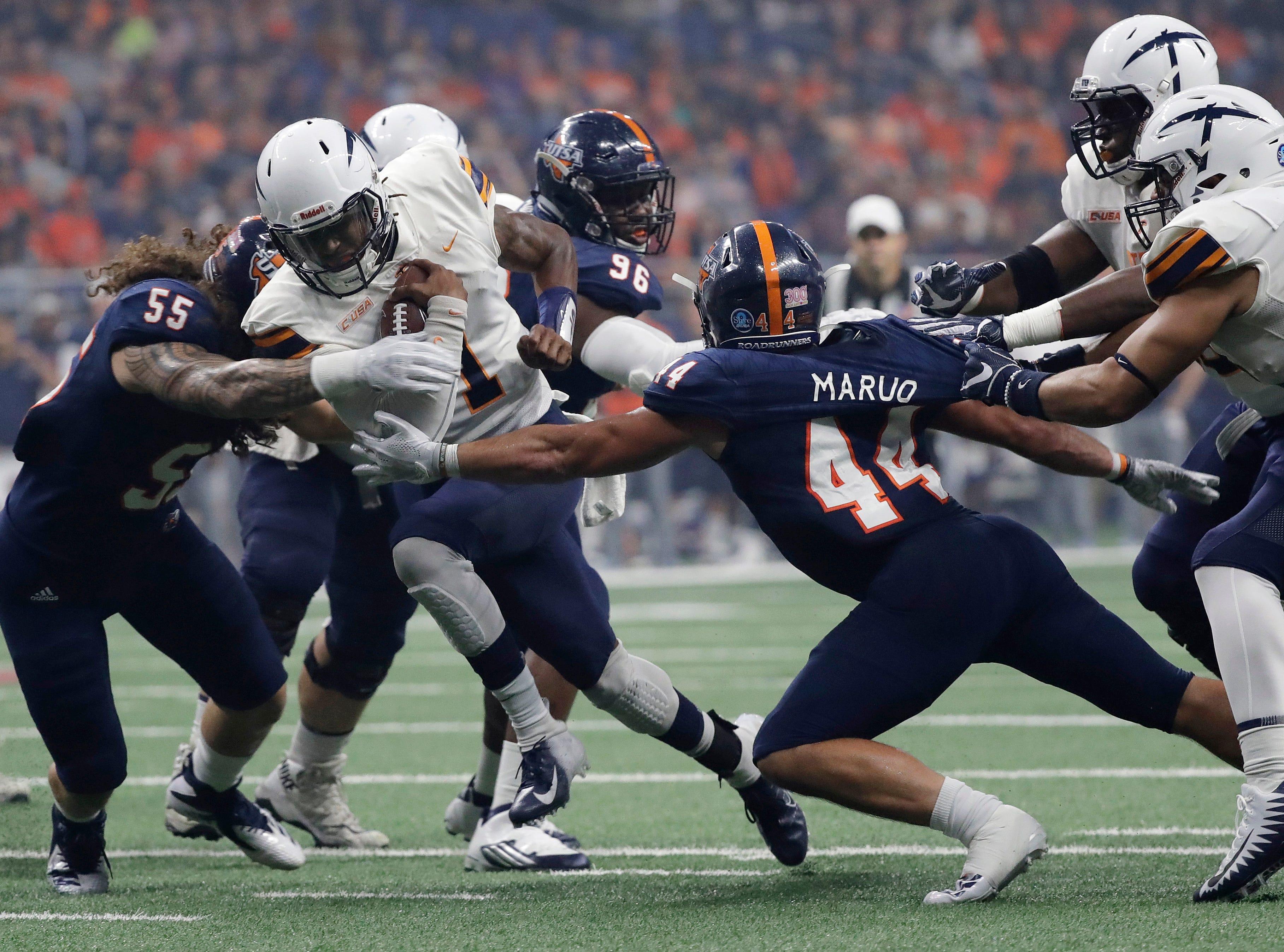 UTEP quarterback Kai Locksley (1) tries to run through UTSA defenders Josiah Tauaefa (55) and Les Maruo (44) during the first half of an NCAA college football game, Saturday, Sept. 29, 2018, in San Antonio. (AP Photo/Eric Gay)