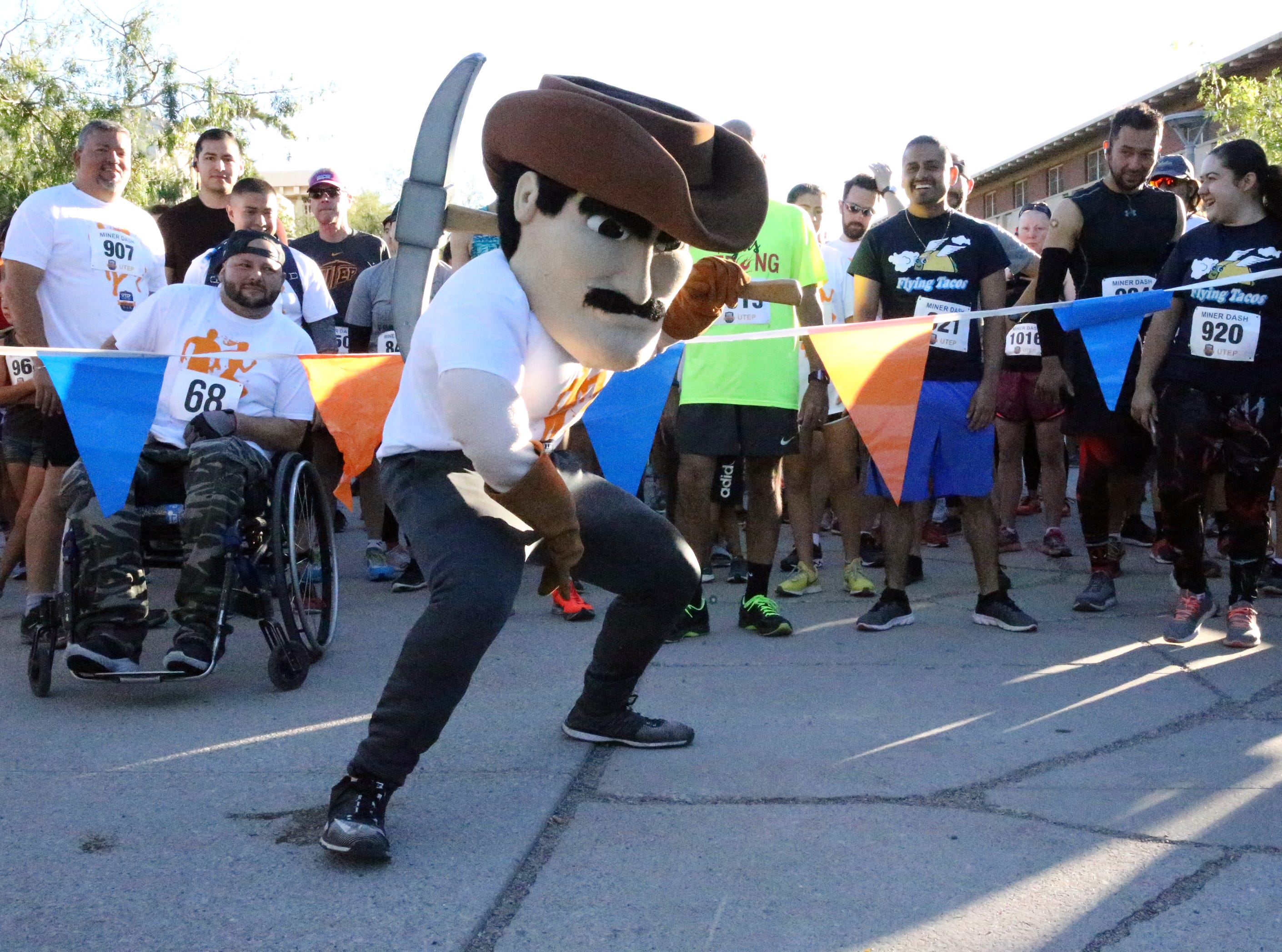 Paydirt Pete urges on runners at the start of the 9th Miner Dash & Family Fiesta Sunday on the UTEP campus. The event kicks off homecoming week.