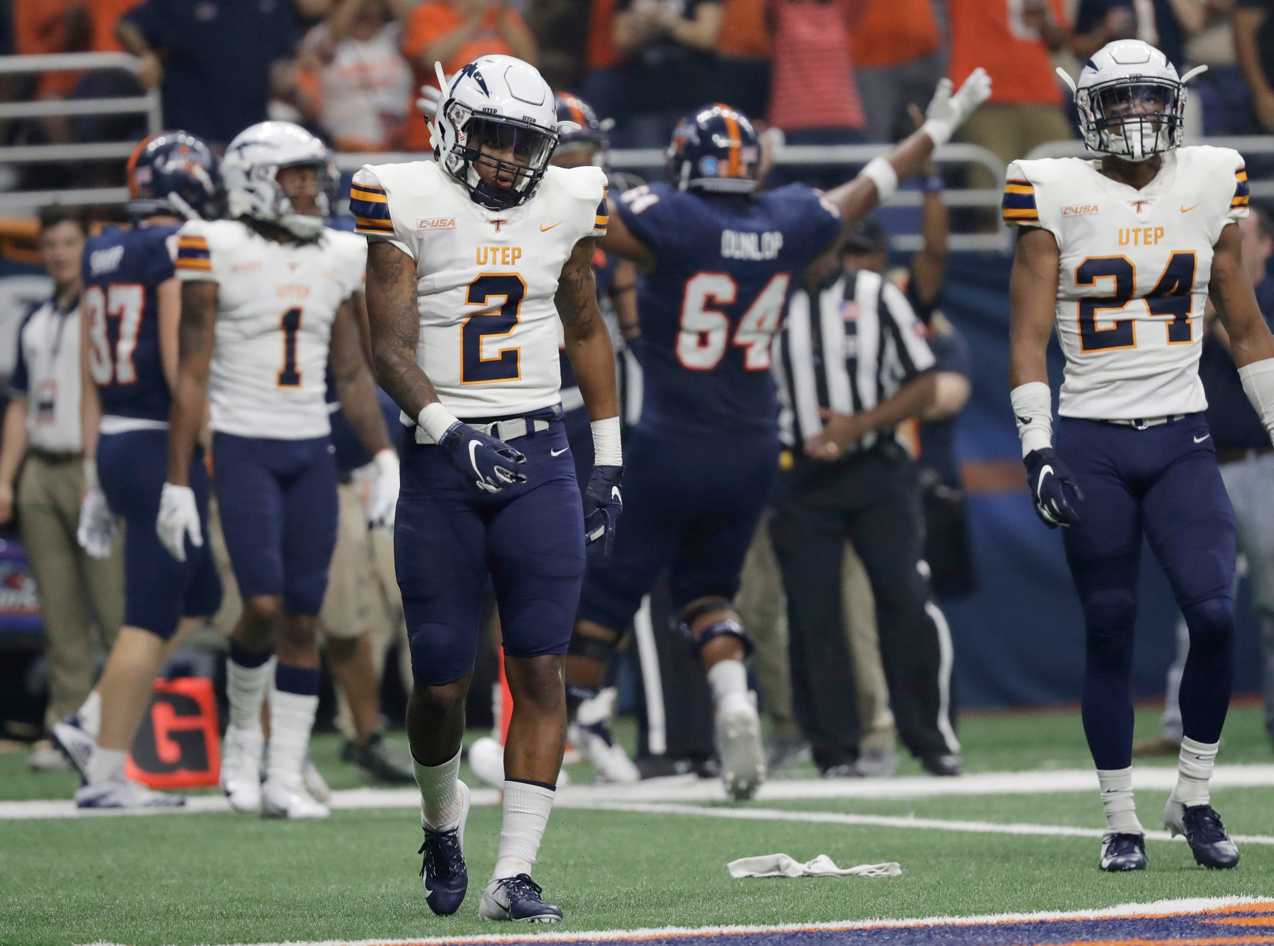 UTEP defenders Kalon Beverly (1), Michael Lewis (2) and Kahani Smith (24) walk off of the field as UTSA players celebrate a touchdown during the first half of an NCAA college football game Saturday, Sept. 29, 2018, in San Antonio. (AP Photo/Eric Gay)