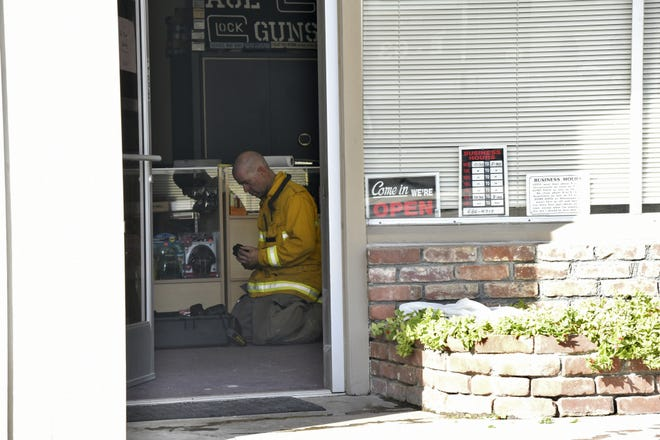 A Tulare firefighter works inside Ace Guns and Ammo after a fire was extinguished above the business on Saturday, September 29, 2018.