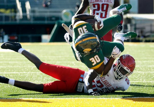 Norfolk State's Aaron Savage (30) goes over Delaware State's Isaiah Small for a   touchdown during an NCAA college football game, Saturday, Sept. 29, 2018, in Norfolk, Va.