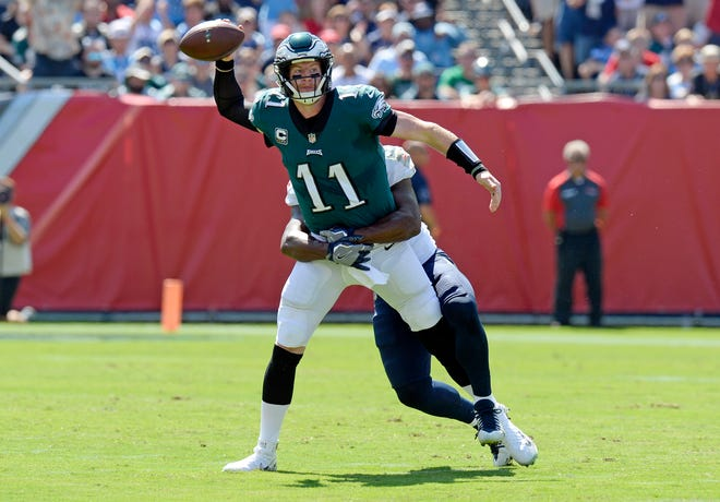 Philadelphia Eagles quarterback Carson Wentz (11) throws a pass as he is grabbed by Tennessee Titans linebacker Jayon Brown in the first half of an NFL football game Sunday, Sept. 30, 2018, in Nashville, Tenn. (AP Photo/Mark Zaleski)