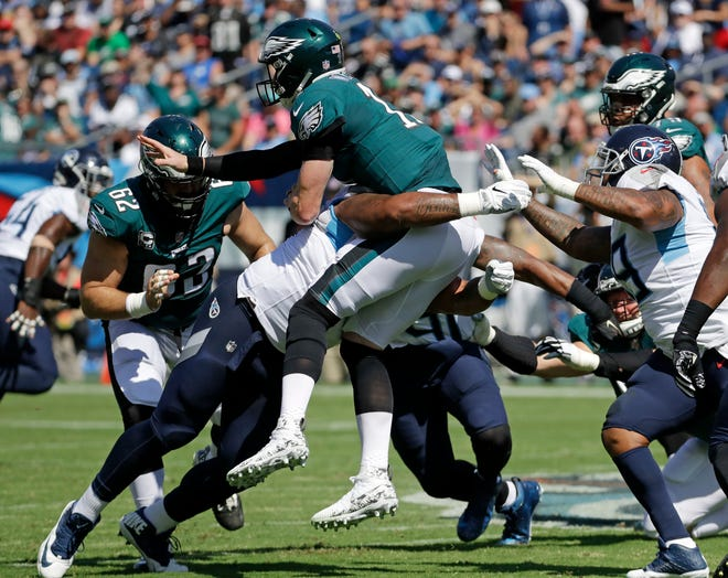 Philadelphia Eagles quarterback Carson Wentz (11) is hit as he throws a pass against the Tennessee Titans in the first half of an NFL football game Sunday, Sept. 30, 2018, in Nashville, Tenn. (AP Photo/James Kenney)