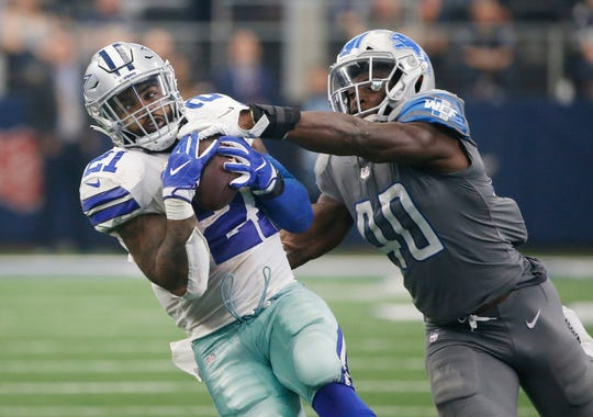 Dallas Cowboys running back Ezekiel Elliott (21) catches a pass as Detroit Lions linebacker Jarrad Davis (40) defends in the second half of an NFL football game in Arlington, Texas, Sunday, Sept. 30, 2018. Dallas won 26-24. (AP Photo/Ron Jenkins)