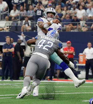 Dallas Cowboys quarterback Dak Prescott, rear, is tackled by Detroit Lions linebacker Devon Kennard (42) after a pass in the second half of an NFL football game in Arlington, Texas, Sunday, Sept. 30, 2018. (AP Photo/Eric Gay)