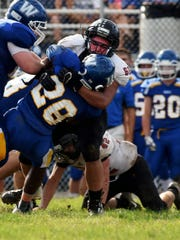 Crooksville's Kenny Wood makes a tackle for loss against Vincent Warren.