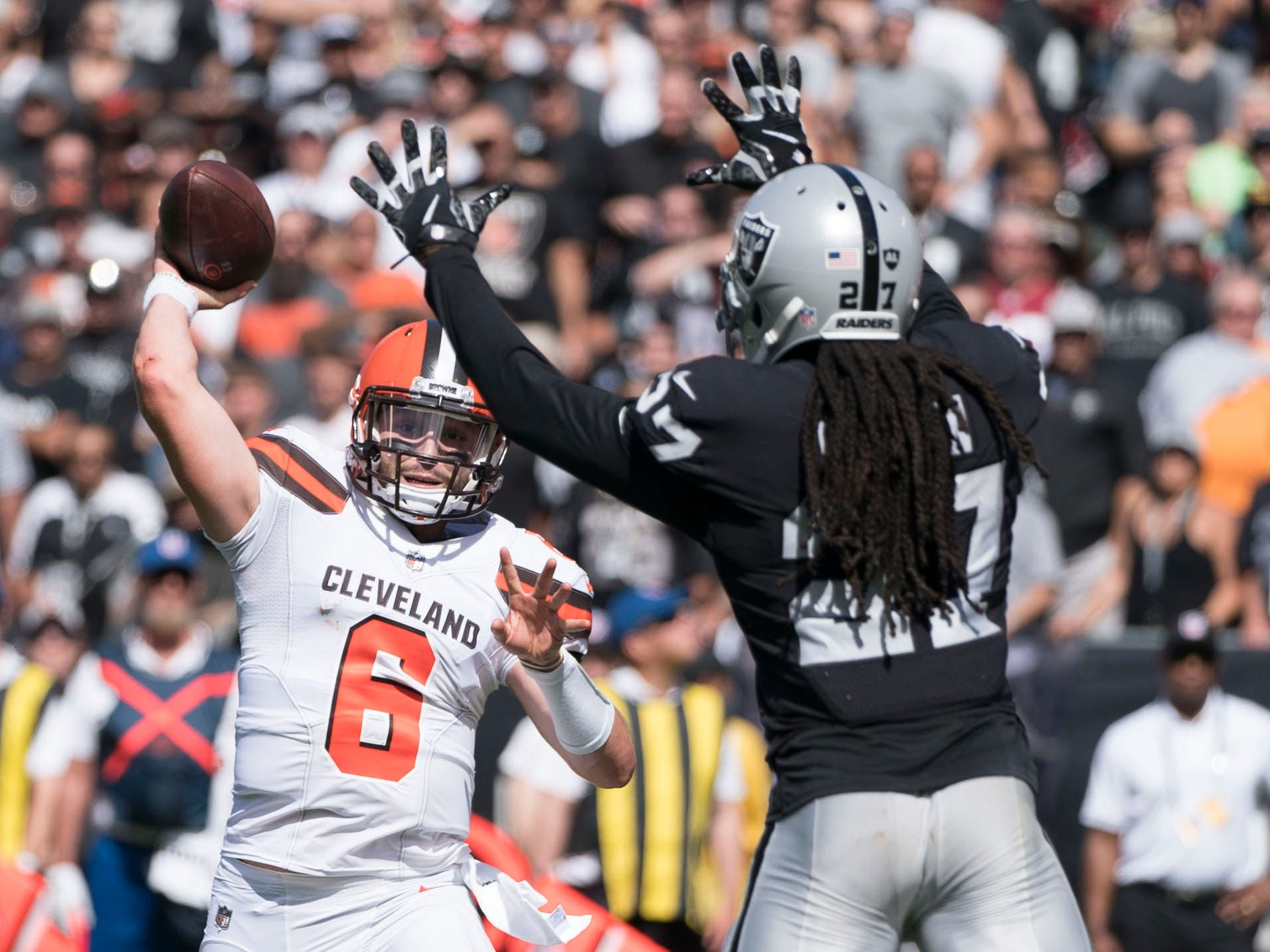 Cleveland Browns quarterback Baker Mayfield passes the football against Oakland Raiders defensive back Reggie Nelson during the first quarter at Oakland Coliseum.
