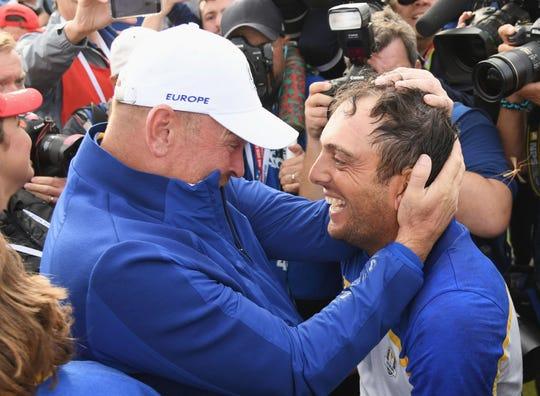 Francesco Molinari of Europe celebrates winning the Ryder Cup with captain Thomas Bjorn.