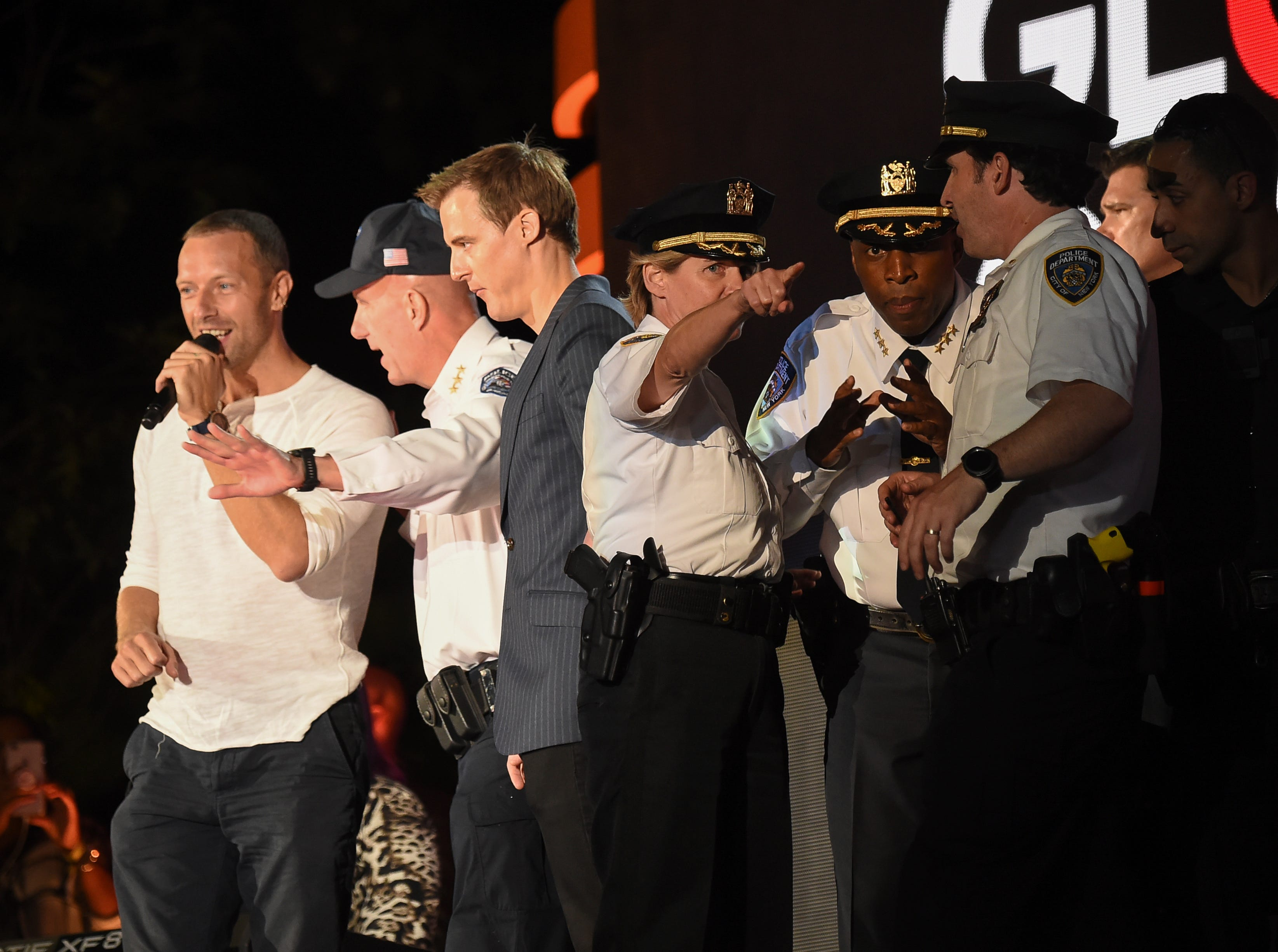 Police officials huddle on stage as Chris Martin addresses the audience after the crowd panic at the 2018 Global Citizen Festival in Central Park on Saturday, Sept. 29, 2018, in New York. Fearing possible gunshots, it took only the collapse of a police barrier at the show Saturday to send thousands of spectators fleeing in panic. Authorities quickly took the stage, assuring the crowd they were safe.  (Photo by Evan Agostini/Invision/AP) ORG XMIT: NYEA0146
