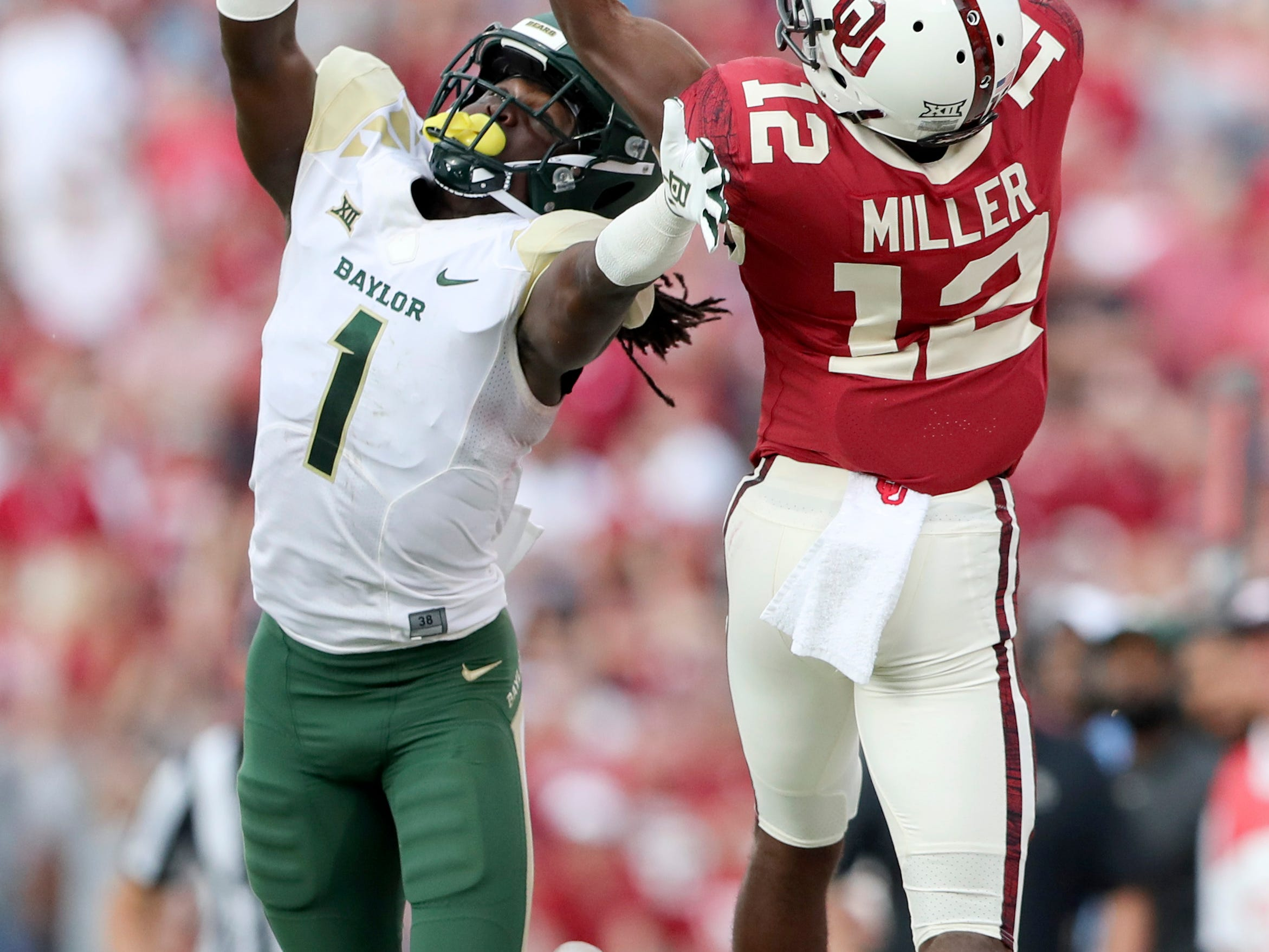 Oklahoma Sooners wide receiver A.D. Miller (12) attempts to catch a pass as Baylor Bears safety Verkedric Vaughns (1) defends during the second half  at Gaylord Family-Oklahoma Memorial Stadium.