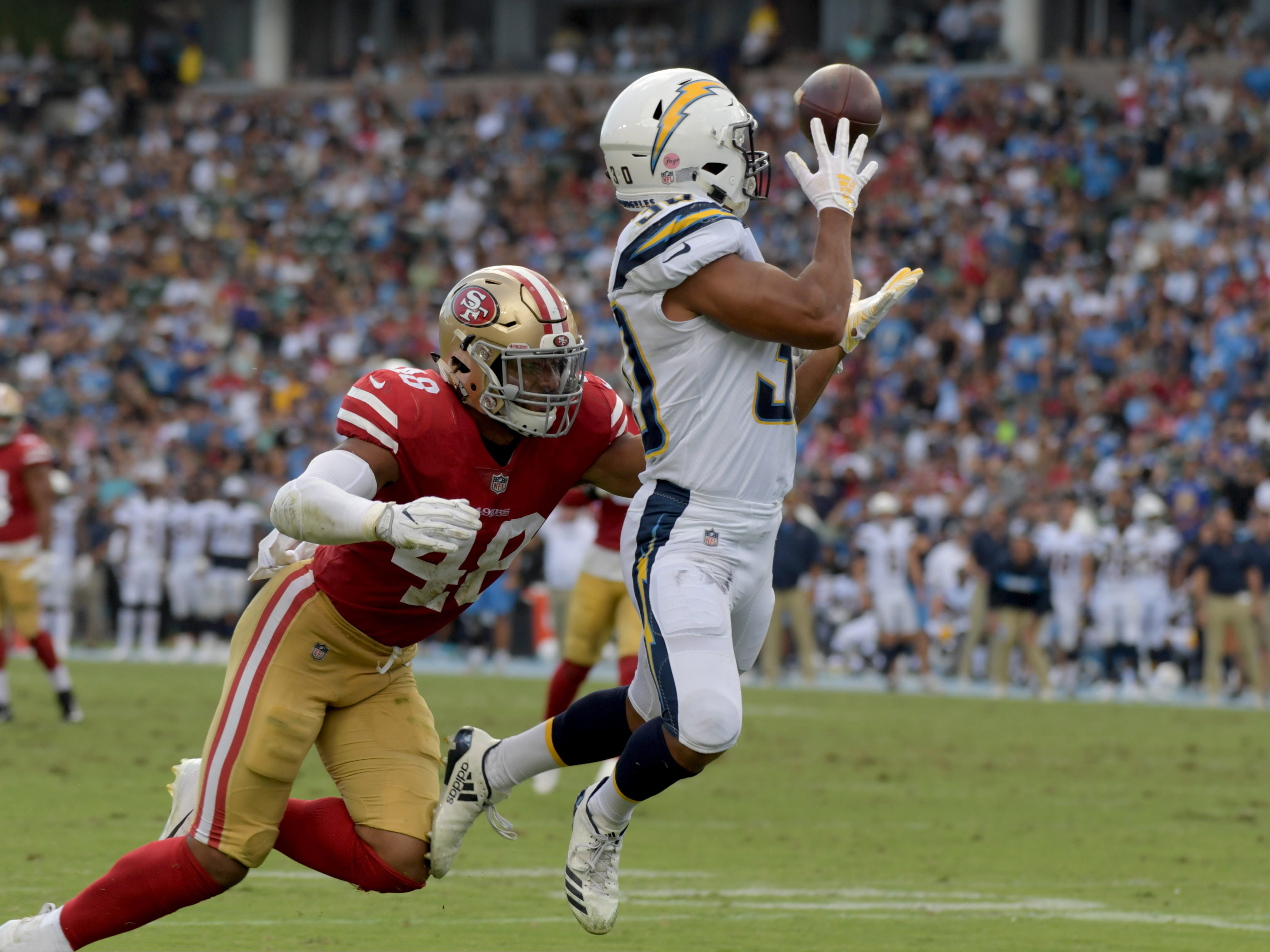 Los Angeles Chargers running back Austin Ekeler is tackled by San Francisco 49ers linebacker Fred Warner in the first half at StubHub Center.