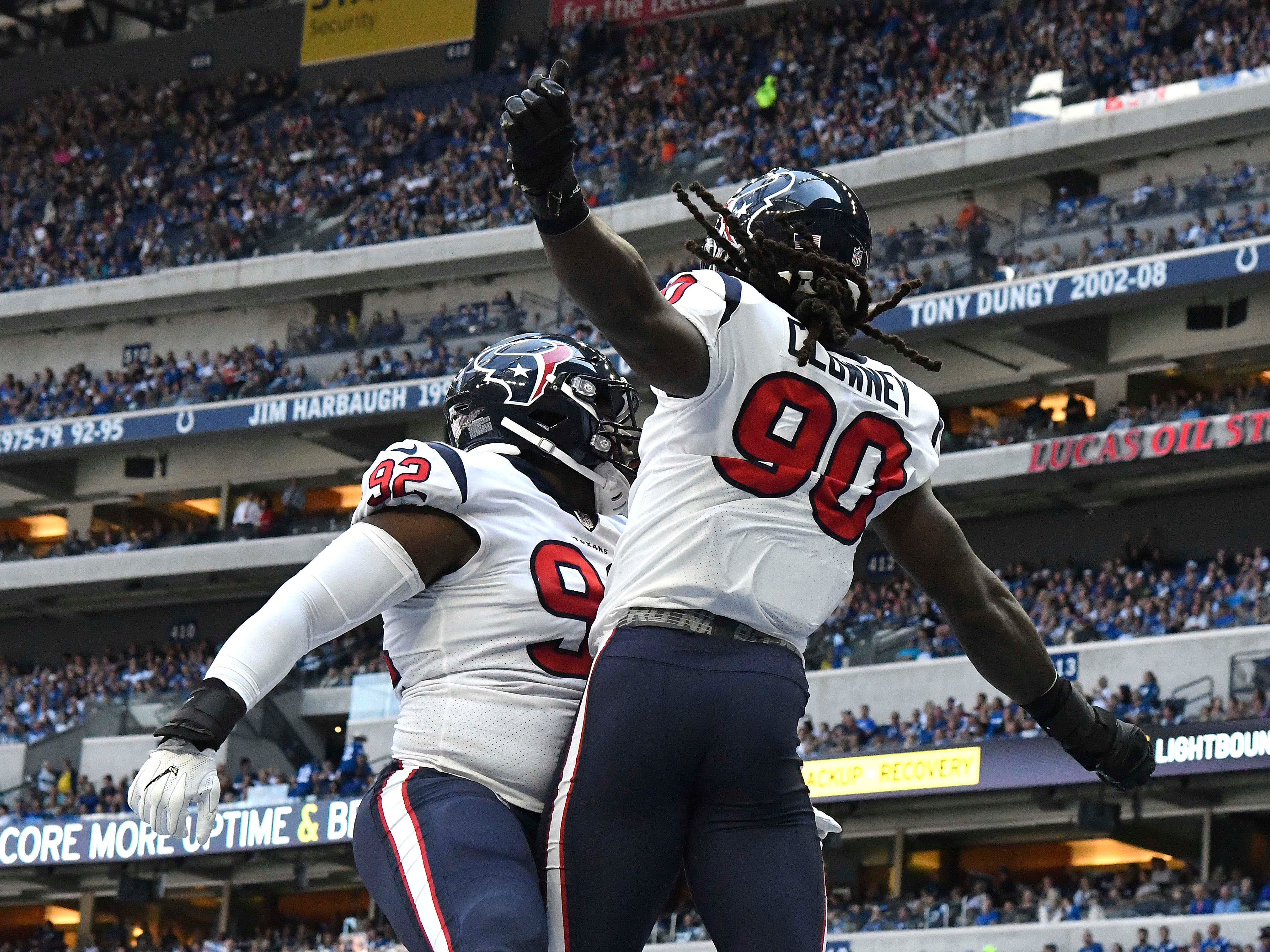 Texans linebacker Jadeveon Clowney (90) celebrates with defensive tackle Brandon Dunn (92) after recovering a fumble for a touchdown.